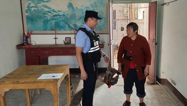 怎幺回事,谕兴一警察拎着一只大公鸡走进居民家中